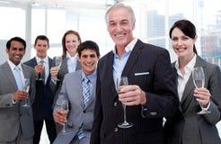 Vetri sorridenti della holding della squadra di affari di Chamoagne Immagine Stock Libera da Diritti