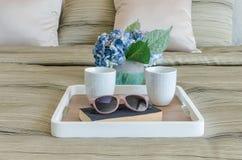 Vetri sul libro nero con la tazza di caffè in vassoio e vaso di legno Immagine Stock Libera da Diritti