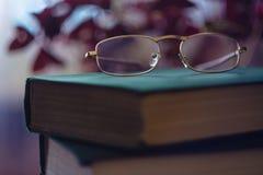 Vetri sul Libro verde Concetto della lettura Primo piano degli occhiali sul fondo di pendenza con il riverbero Fuoco selettivo fotografia stock