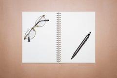 Vetri, taccuino e penna su una carta marrone Immagini Stock Libere da Diritti