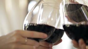 Vetri tintinnanti con vino rosso e la tostatura stock footage