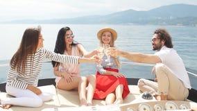 Vetri tintinnanti degli amici felici di champagne e della navigazione sull'yacht video d archivio