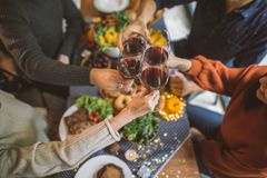 Vetri tintinnanti degli amici sopra alimento sulla tavola di cena fotografia stock libera da diritti