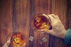 Vetri tintinnanti degli uomini di whiskey nella notte del partito Immagini Stock