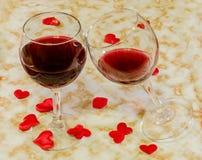 Vetri trasparenti con vino rosso ed i cuori rossi del biglietto di S. Valentino del tessuto, vecchio fondo di carta, fine su Immagini Stock