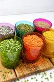 Vetri trasparenti multicolori con i vari legumi (piselli, con riferimento a immagine stock