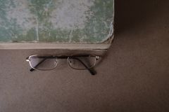 Vetri vicino al vecchio libro con i bordi lacerati e la copertura misera Il concetto di lettura e di istruzione Vista superiore,  immagini stock