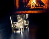 Vetri vuoti di whiskey con i cubetti di ghiaccio davanti al camino Fotografia Stock Libera da Diritti