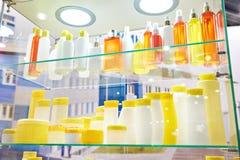Vetrina del negozio con le bottiglie e lo sciampo cosmetici di plastica Immagine Stock