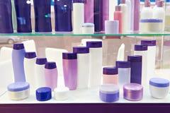Vetrina del negozio con le bottiglie e lo sciampo cosmetici di plastica Fotografie Stock Libere da Diritti