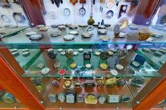 Vetrina di vetro antica con molti movimenti differenti dell'orologio come pure un orologio d'attaccatura nei precedenti Fotografia Stock