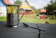 Vetro antico con tè ed il cucchiaio all'aperto Fotografie Stock Libere da Diritti