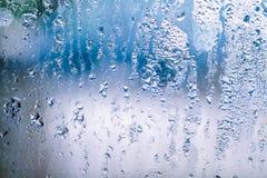 Vetro appannato con le gocce di acqua su fondo blu immagini stock libere da diritti