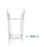 Vetro con acqua e un mucchio dei ridurre in pani, pillole Immagine Stock