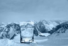Vetro con acqua ed i cubetti di ghiaccio sui precedenti di una cresta nevosa della montagna, tonalità fredda immagini stock
