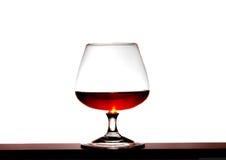 Vetro con brandy su una priorità bassa bianca Fotografia Stock Libera da Diritti