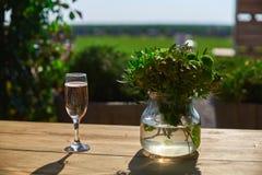 Vetro con champagne su una tavola di legno, giorno soleggiato Immagine Stock