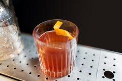 Vetro con il cocktail e la scorza d'arancia al contatore della barra Fotografia Stock Libera da Diritti