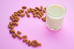 Vetro con il latte e le mandorle dell'avena su un fondo rosa pastello fotografia stock libera da diritti