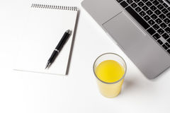 Vetro con Juice And Notebook With Pen vicino al computer portatile Immagine Stock