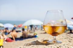 Vetro con la bevanda sulla spiaggia di estate Immagini Stock Libere da Diritti