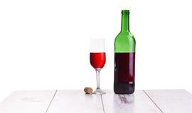 Vetro con la bottiglia del vino rosso sul vino rosso elegante e costoso bianco del fondo, di vetro e della bottiglia Fotografie Stock Libere da Diritti