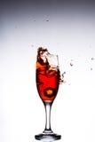Vetro con le cadute di ghiaccio rosse del cocktail sui precedenti grigi bianchi Fotografia Stock