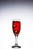 Vetro con le cadute di ghiaccio rosse del cocktail sui precedenti grigi bianchi Fotografie Stock