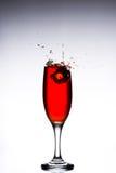 Vetro con le cadute di ghiaccio rosse del cocktail sui precedenti grigi bianchi Fotografie Stock Libere da Diritti