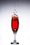 Vetro con le cadute di ghiaccio rosse del cocktail sui precedenti grigi bianchi Fotografia Stock Libera da Diritti