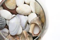 Vetro con le pietre e le coperture su fondo bianco isolato Fotografia Stock Libera da Diritti