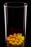 Vetro con le pillole rotonde gialle Fotografia Stock