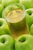Vetro con spremuta su una priorità bassa delle mele Fotografia Stock