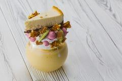 Vetro con un frappé con una torta di formaggio sulla cima fotografia stock