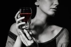 Vetro con un vino rosso in una mano femminile Fotografie Stock Libere da Diritti