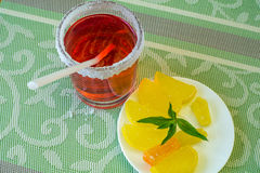 Vetro con una bevanda e un piattino con la caramella della frutta Fotografie Stock