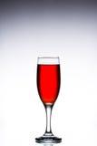 Vetro con vino rosso su un fondo grigio bianco Fotografia Stock