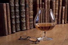 Vetro dei libri dell'annata e del cognac fotografie stock libere da diritti