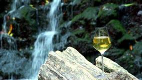 Vetro dei supporti del vino bianco su una superficie di legno nei precedenti una roccia con una cascata stock footage