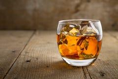 Vetro del brandy del whiskey scozzese con ghiaccio sulla superficie rustica del barilotto della tavola di legno della barra Fotografie Stock Libere da Diritti