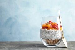 Vetro del budino saporito del seme di chia con granola, il cachi ed il melograno sulla tavola fotografie stock libere da diritti