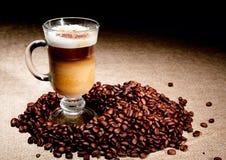 Vetro del Cappuccino con i chicchi di caffè Fotografie Stock Libere da Diritti
