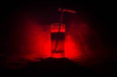 Vetro del cocktail alcolico rosso su fondo scuro con fumo e la lampadina Coctail caldo del fuoco concetto del club Fotografia Stock