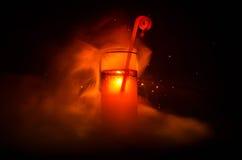 Vetro del cocktail alcolico rosso su fondo scuro con fumo e la lampadina Coctail caldo del fuoco concetto del club Fotografie Stock Libere da Diritti