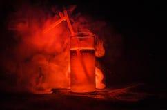 Vetro del cocktail alcolico rosso su fondo scuro con fumo e la lampadina Coctail caldo del fuoco concetto del club Immagine Stock Libera da Diritti