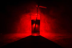 Vetro del cocktail alcolico rosso su fondo scuro con fumo e la lampadina Coctail caldo del fuoco concetto del club Fotografie Stock