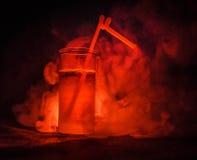 Vetro del cocktail alcolico rosso su fondo scuro con fumo e la lampadina Coctail caldo del fuoco concetto del club Fotografia Stock Libera da Diritti