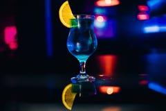 Vetro del cocktail blu Martini dell'alcool con una fetta di partito arancio alla barra Fotografia Stock Libera da Diritti