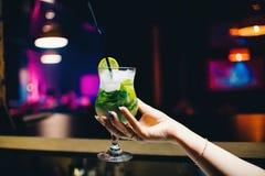 Vetro del cocktail di Mojito in mano femminile con calce e la menta Fotografia Stock Libera da Diritti