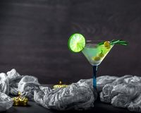Vetro del cocktail sulla tavola Olive, rosmarini e calce in un g Fotografia Stock